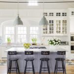 imagem de uma cozinha americana com um balcão e cadeiras no meio