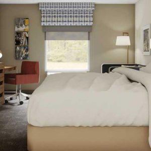 imagem de um quarto pequeno com uma cama de casal