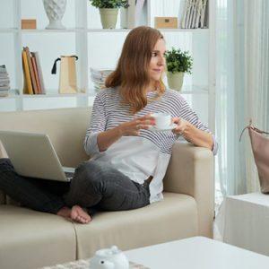 mulher sentadlado no sofá da sala com um notebook no colo e segurando um xícara
